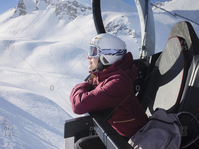 Young woman skier wearing helmet and ski goggles looking out from ski lift,  Alpe Ciamporino, Piemonte, Italy