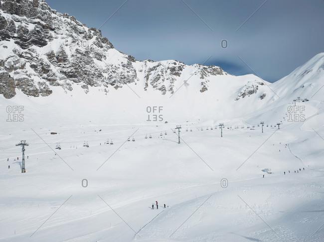 Ski lift in snow covered mountain valley landscape,  Alpe Ciamporino, Piemonte, Italy