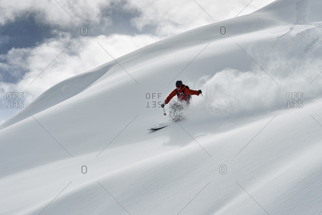 Male skier skiing down snow covered mountain, Alpe-d'Huez, Rhone-Alpes, France