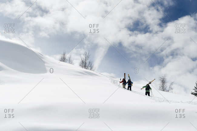 Male skiers trudging up snow covered mountain, rear view, Alpe-d'Huez, Rhone-Alpes, France