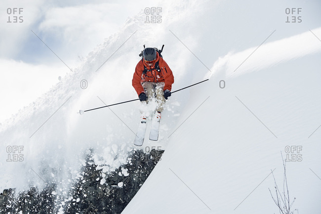 Male skier skiing mid air down snow covered mountain, Alpe-d'Huez, Rhone-Alpes, France