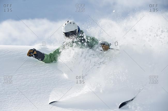 Male skier speeding down snow covered mountain, Alpe-d'Huez, Rhone-Alpes, France