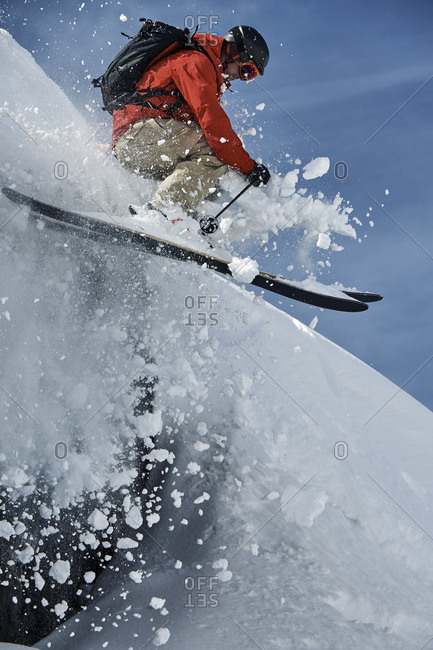Male skier skiing mid air down steep snow covered mountain, Alpe-d\'Huez, Rhone-Alpes, France