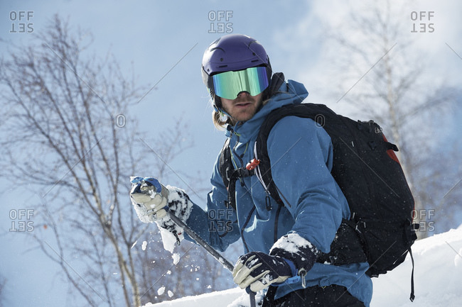 Male skier looking back on mountainside, Alpe-d'Huez, Rhone-Alpes, France