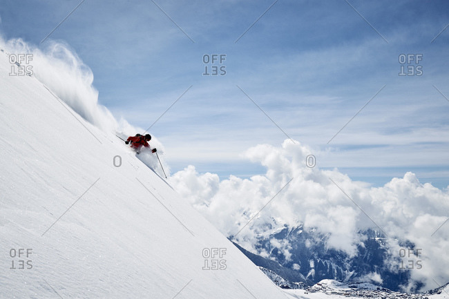 Landscape with male skier skiing down steep mountainside, Alpe-d\'Huez, Rhone-Alpes, France