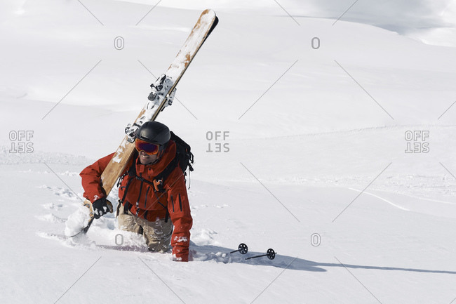 Male skier trudging up mountain through deep snow, Alpe-d'Huez, Rhone-Alpes, France
