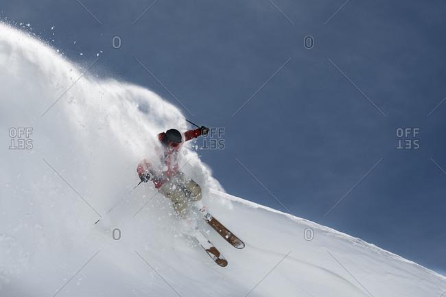 Male skier skiing down steep mountainside, Alpe-d\'Huez, Rhone-Alpes, France
