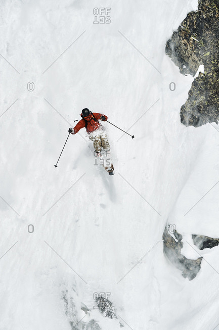 Male skier skiing down vertical mountainside, Alpe-d\'Huez, Rhone-Alpes, France