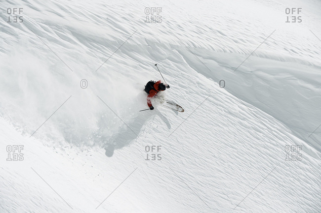 Male skier skiing down mountainside, high angle view, Alpe-d\'Huez, Rhone-Alpes, France