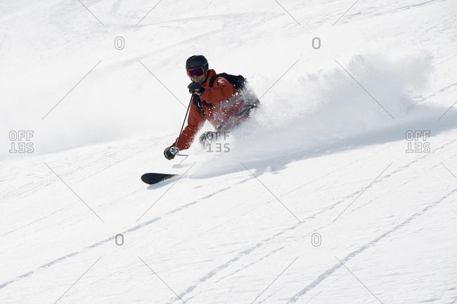 Male skier skiing down mountain, Alpe-d\'Huez, Rhone-Alpes, France