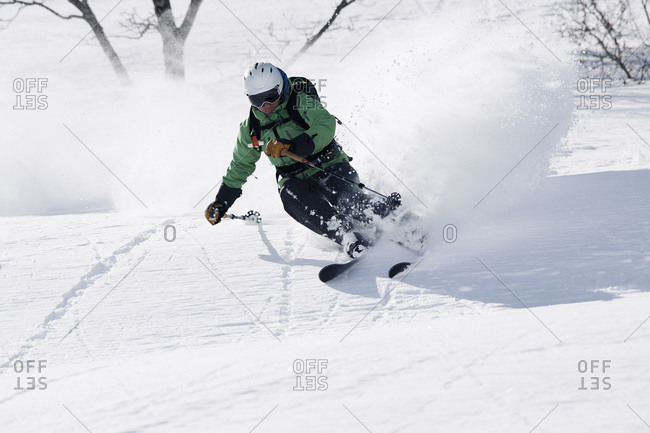 Male skier swerve skiing down mountain, Alpe-d'Huez, Rhone-Alpes, France