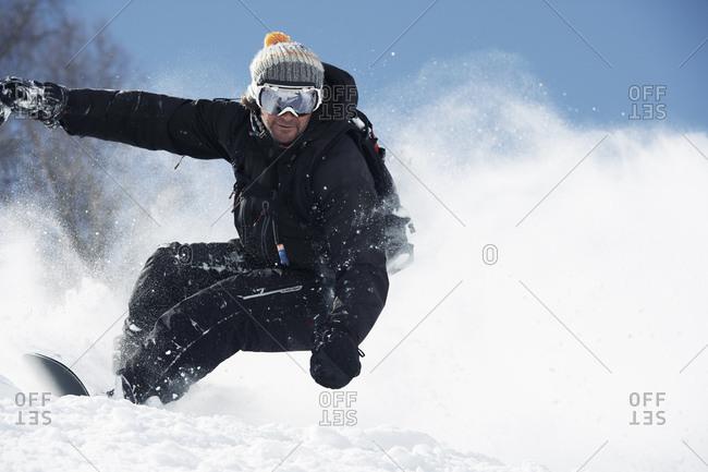 Male snowboarder speeding down mountainside, Alpe-d'Huez, Rhone-Alpes, France