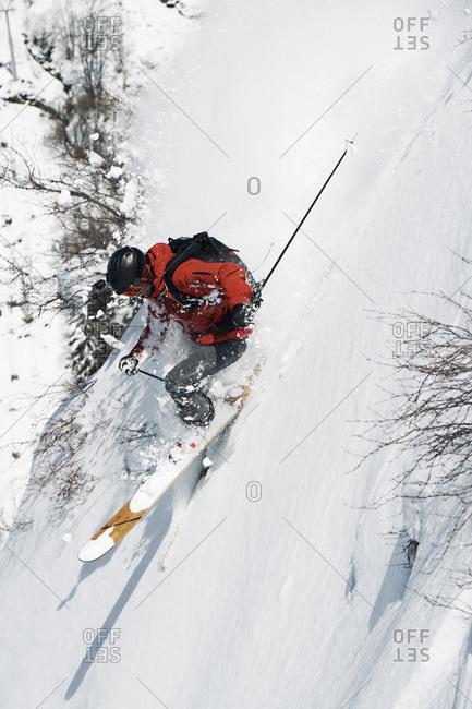 Male skier speeding down vertical mountainside, Alpe-d'Huez, Rhone-Alpes, France
