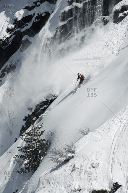 Male skier speeding down rugged vertical mountainside, Alpe-d'Huez, Rhone-Alpes, France