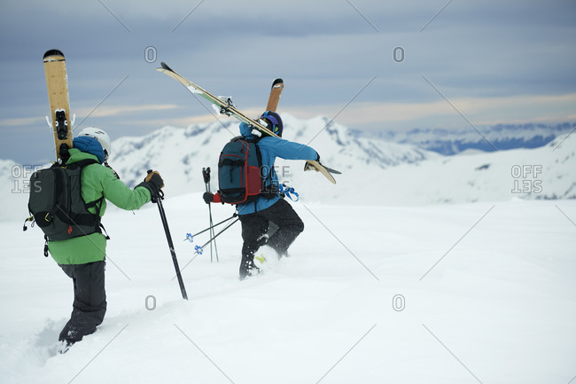 Landscape with two male skiers trudging toward mountain, rear view, Alpe-d'Huez, Rhone-Alpes, France