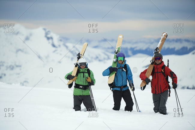 Landscape with three male skiers carrying skis, Alpe-d'Huez, Rhone-Alpes, France