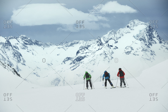 Landscape with three male skiers skiing toward mountain, rear view, Alpe-d'Huez, Rhone-Alpes, France