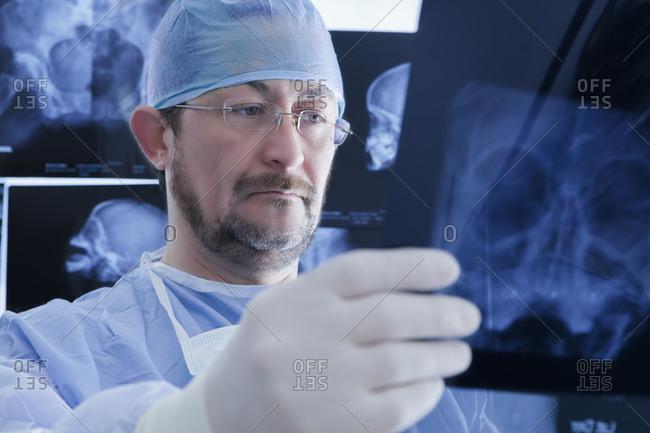 Surgeon closely examining X-ray image