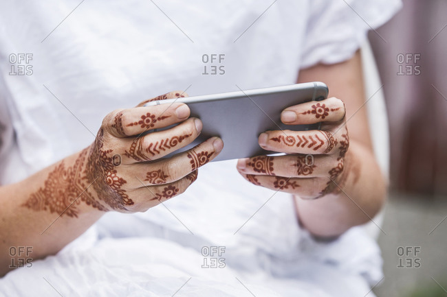 Woman with henna tattoo on hands using smartphone