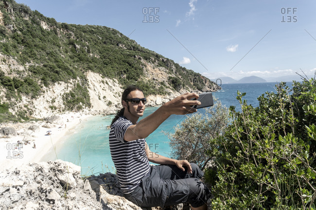 Man taking selfie on cliff top, Lefkada Island, Levkas, Greece
