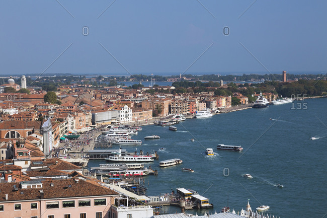 April 28, 2016: Water taxis and vaporettos along Riva degli Schiavoni promenade, old Renaissance architectural style residential buildings and palaces, Venice, Veneto, Italy