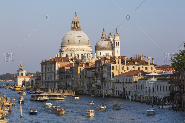 April 28, 2016: Water taxis and vaporettos on Grand Canal, Renaissance architectural style palace buildings, Santa Maria della Salute basilica, Dorsoduro, Venice, Veneto, Italy