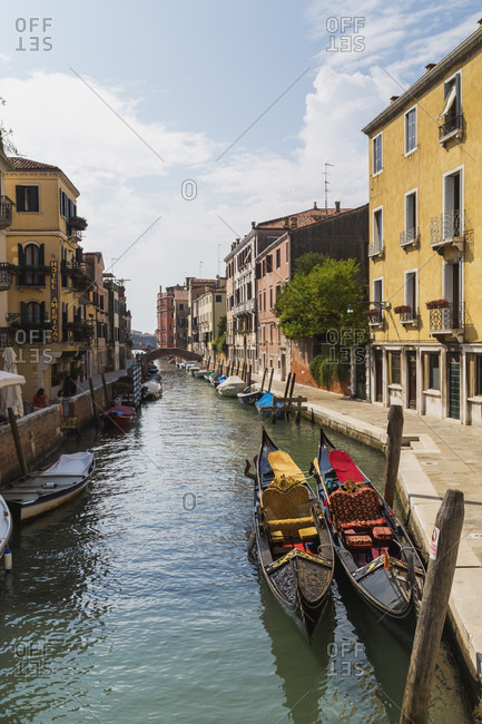 April 28, 2016: Gondolas moored on canal lined with yellow and pink old architectural residential buildings, St Mark's square, Venice, Veneto, Italy