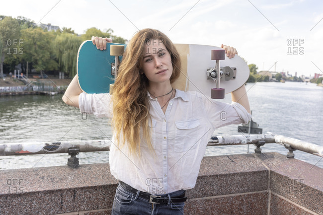 Young woman with skateboard on shoulder, river in background, Berlin, Germany