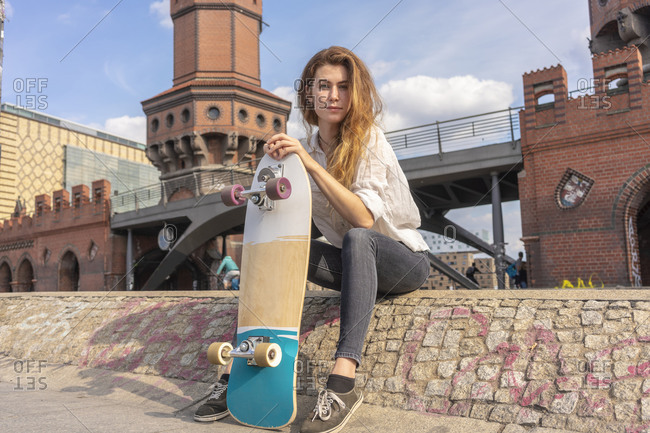 Young woman with skateboard resting on Oberbaum bridge in city, Berlin, Germany