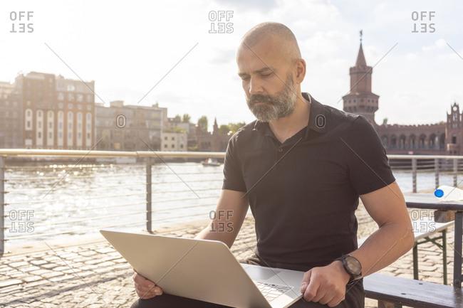 Man using laptop on bridge, river, Oberbaum bridge and buildings in background, Berlin, Germany