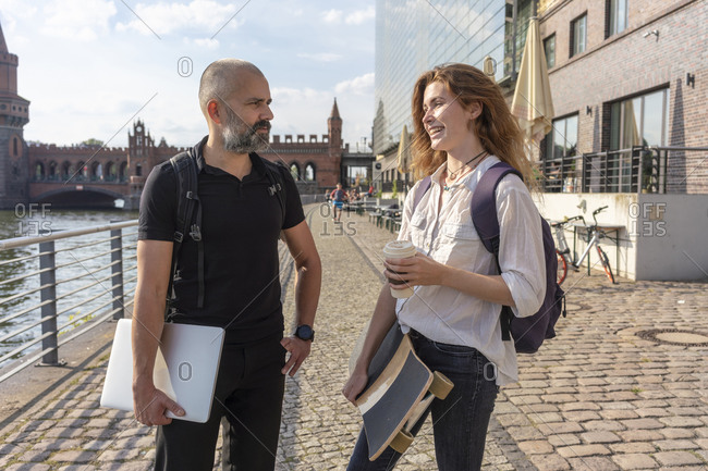 Man talking to female friend with skateboard on bridge, river, Oberbaum bridge and buildings in background, Berlin, Germany