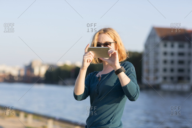 Young woman taking photograph with smartphone by river in summer, Berlin, Germany
