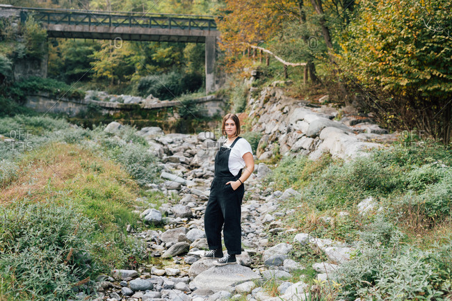Woman standing in dry riverbed, Rezzago, Lombardy, Italy