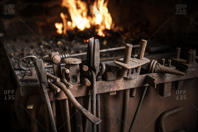 Row of tools in front of fire in blacksmiths workshop