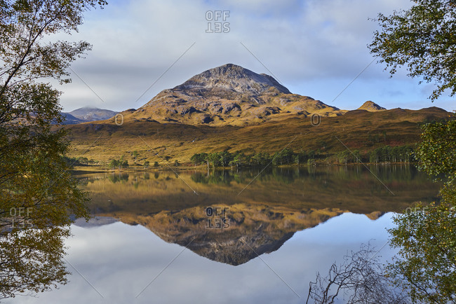 Tranquil mountain landscape mirror imaged in loch, Achnasheen, Scottish Highlands, Scotland