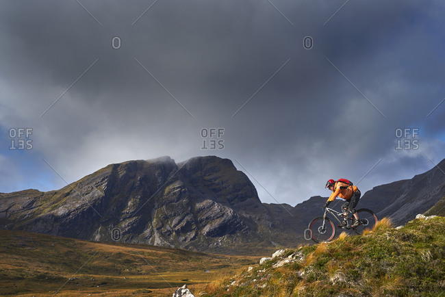 Male mountain biker biking down mountain landscape,  Achnasheen, Scottish Highlands, Scotland