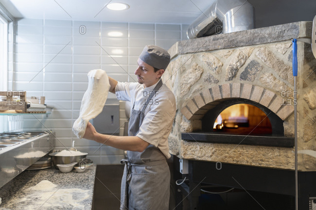 Chef tossing and stretching the dough for Pinsa Romana, a Roman style pizza blend reducing sugar and saturated fat, containing rice and soy with less gluten
