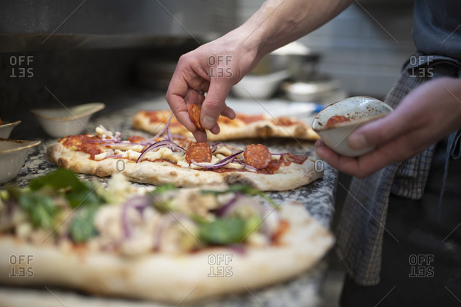Chef placing sausage onto Pinsa Romana base, a Roman style pizza blend reducing sugar and saturated fat, containing rice and soy with less gluten, close up of hands