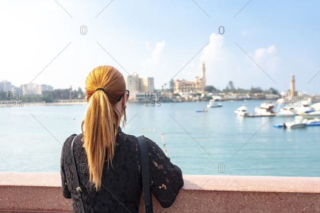 Female tourist with red hair looking out over sea toward Montaza palace, rear view, Alexandria, Egypt