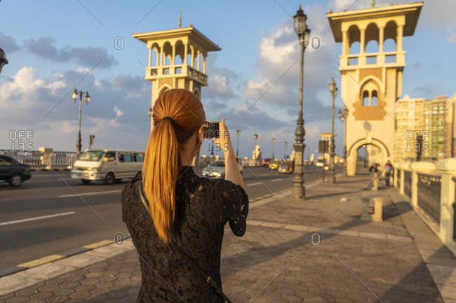Female tourist with red hair photographing Stanley bridge, rear view, Alexandria, Egypt
