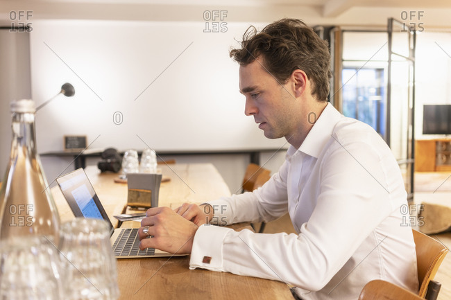Mid adult businessman typing on laptop at office desk