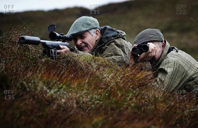 Man and gamekeeper deer stalking on moorland, Scottish Highlands