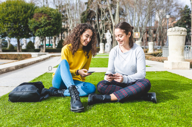 Girlfriends reading message on smartphone in city park, Madrid, Spain