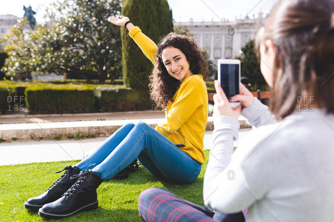 Girlfriends taking photograph in city park, Madrid, Spain