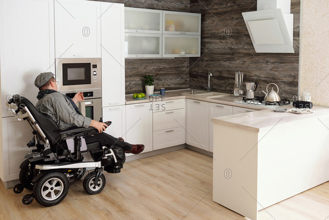 Physically impaired man switching on oven in kitchen