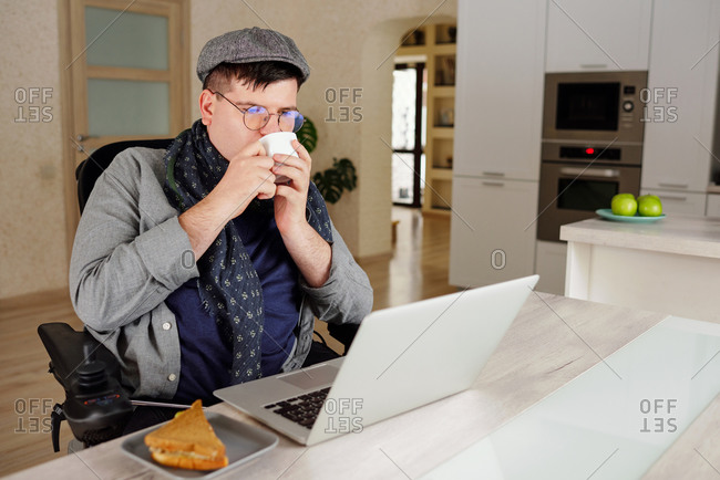 Physically impaired man drinking and working on laptop at home