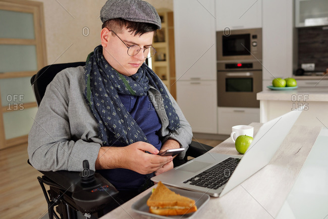 Physically impaired man using smartphone at home