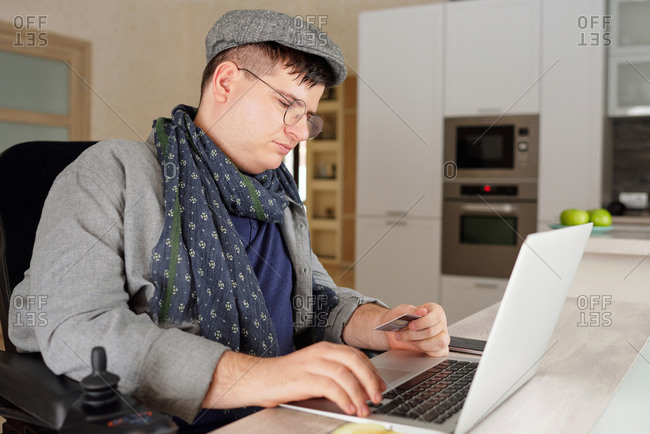 Physically impaired man making online purchase on laptop at home