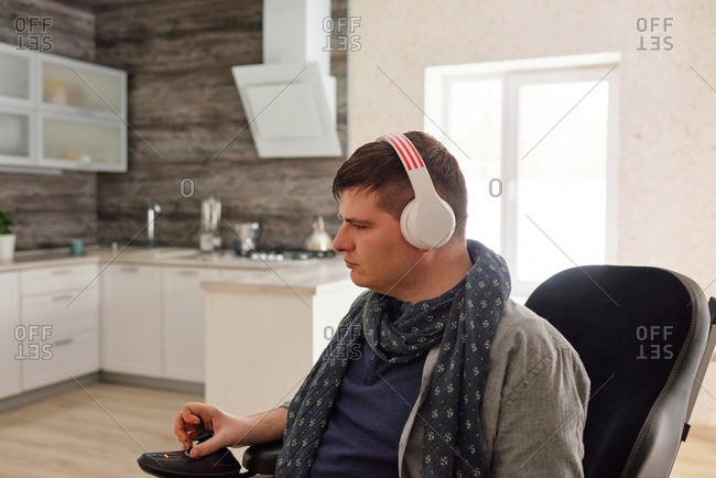 Physically impaired man listening to music with headphones at home