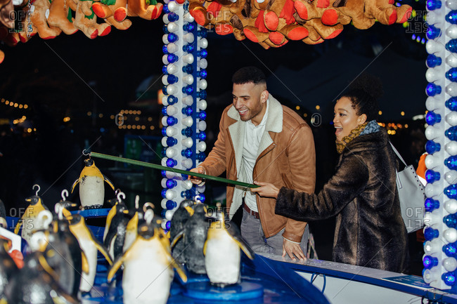 Couple trying to hook a penguin on a fairground stall